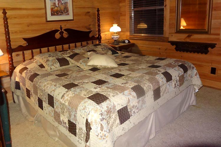 The bedroom features a king size bed with handmade quilt